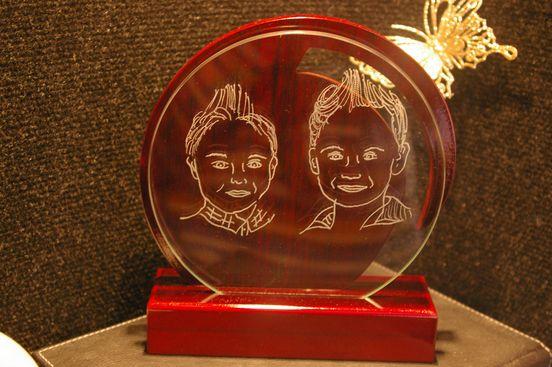 Portraits de 2 enfants graves sur un trophee bois et verre